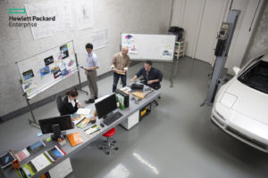 High angle view of creative businessmen and businesswoman working in car design meeting in modern office